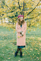 Smiling trendy girl posing in park