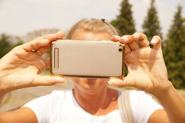 A young woman is taking a picture with a smartphone.