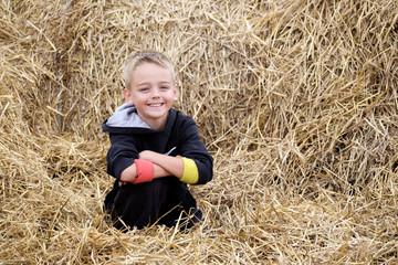 Boy in hay bundles