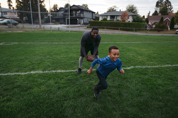Adult and kid playing football together outside in field