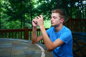Young Man Using Cellphone On Deck At Cabin