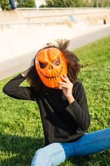 Girl wearing Halloween mask on green grass.