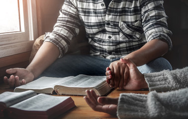 Two young christianity sitting around wooden table and holding hands for praying to God together.
