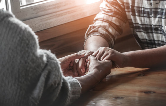 Two christianity sitting around wooden table and holding hands with praying to God together.