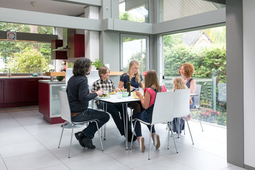 Family and friends eating lunch in a bright modern home.