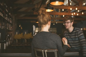 Couple talking to each other at bar counter