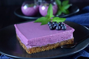 Square mousse cake with bilberries against the dark background