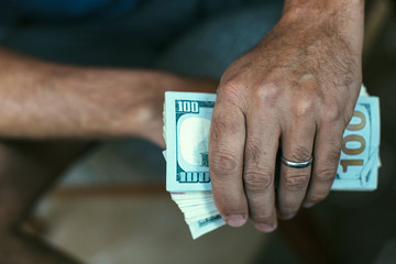 Married man holding a stack of hundred dollar bills