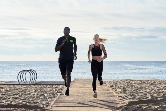 Portrait of running couple on the beach against sea.