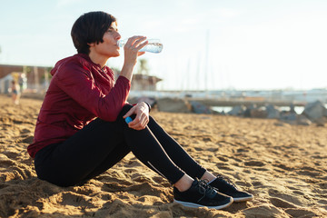 Woman drinking water on the beach after to do sport.