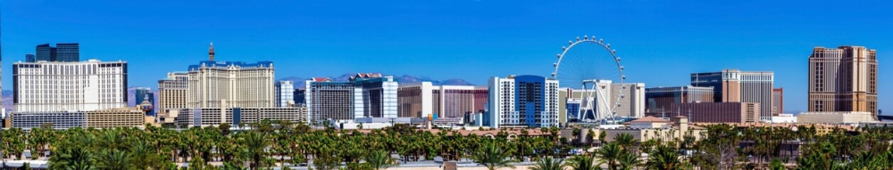 Wall Mural - Panoramic view of Las Vegas strip with landmark resorts and ferris wheel in front of clear blue sky.