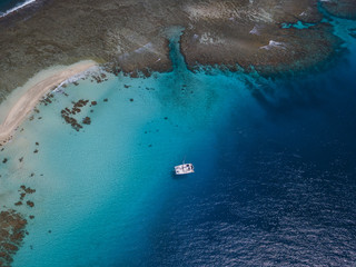 Aerial view of a boat in front of the island. Amazing beach with