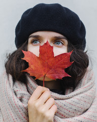 Woman sniffing autumn leaf