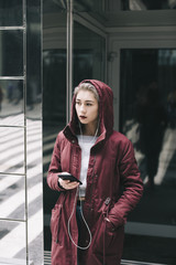 Young woman listening to music on headphones in city