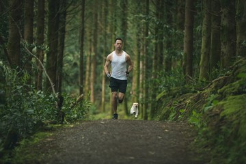 Man jogging in forest with his dog