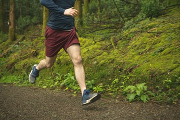 Man jogging in lush forest