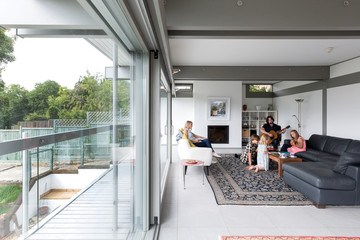 Family relaxing together in a contemporary house with a large area of glass.
