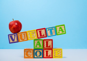 Back to School spelled out in spanish with wooden blocks with apple