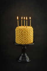 Golden birthday cake with knitted pattern made of fondant and ca