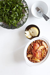 Casserole with tandoori chicken, chickpeas and asian pear with steamed collards on the side, studio shot on white background