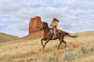 Cowgirl Riding Horse with Castel Rock in the background, Shell, Wyoming, USA