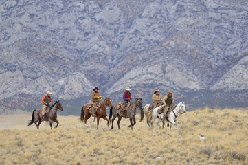 Cowboys and Cowgirls riding horses in wlderness, Rocky Mountains, Wyoming, USA