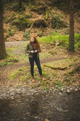 Young female hiker standing near the river coast in the forest