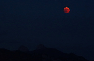 The full moon rises during a total eclipse above the Tour de Mayen and Tour d'Ai in the Swiss Alps in this picture taken from Chardonne
