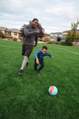 Man and child (father son) playing soccer (football) together in