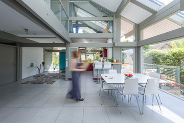 Contemporary housing with woman walking towards the kitchen table.
