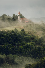 Beautiful landscape with a church into the misty forest in Slovenia