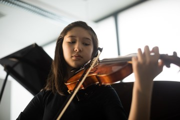 Schoolgirl playing violin in music school