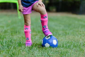 Young girl standing with one foot on top of a soccer ball