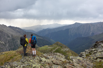 Couple of backpackers looking at the scenic mountains and the stormy sky