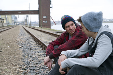 Two teenage boys sitting on railroad tracks together, near harbour, Germany
