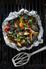 Mussels with yellow, red and orange peppers, red onions and cilantro in a cream sauce in tinfoil on a barbeque grill