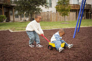 Boy Pulling Brother in Wagon at Playground, Maryland, USA