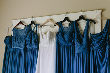 Wedding Dress Hanging next to Bridesmaid Dresses