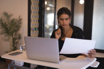Businesswoman reading documents while working on laptop