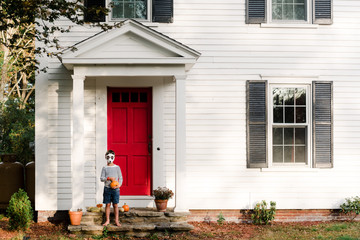 little boy in front of red door with panda bear mask in the fall Fototapete