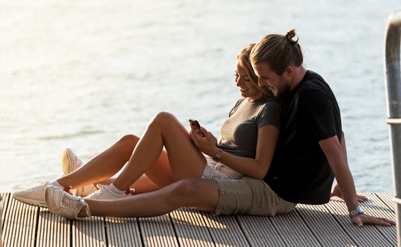 Beautiful young couple using mobile phone on dock of a lake.