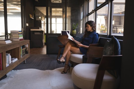 Businesswoman reading document while sitting on sofa