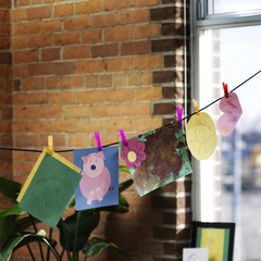Children's Artwork Hanging on Clothesline by Window