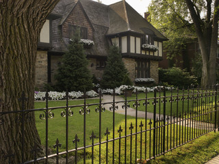 View of iron fence and house exterior in summer, Toronto, Ontario, Canada