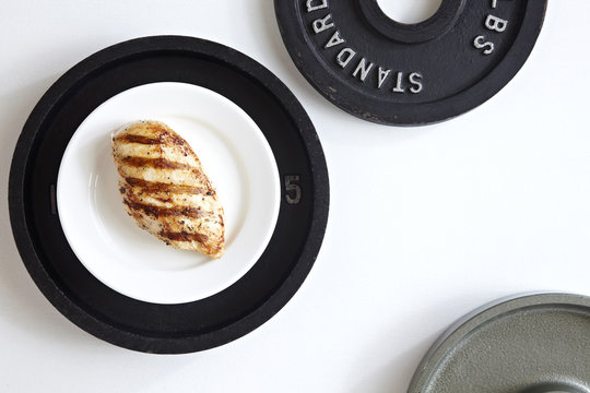 Grilled Chicken breast on a white plate on top of a weight plate, studio shot on white background