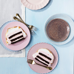 High angle view of slices of Baked Alaska on pink plates with forks, studio shot on blue background