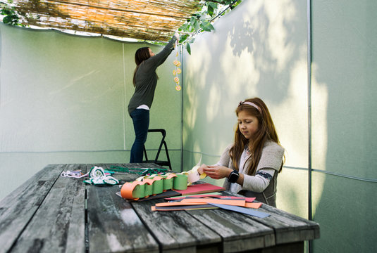 Sukkot: Girl Sits In Sukkah Making Decorations With Paper