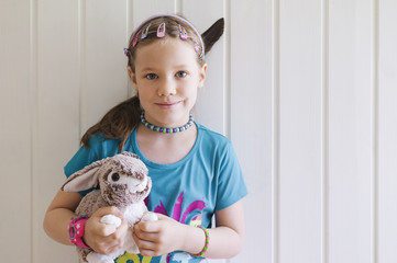 Portrait of young girl standing in front of wall holding her toy bunny, Sweden