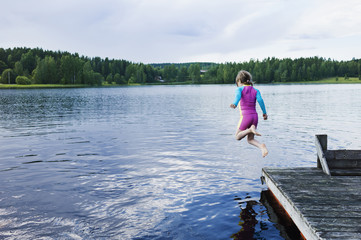 Girl jumping in lake from dock, Sweden
