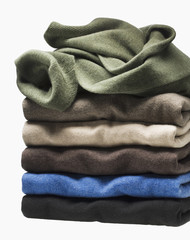 Stack of multi-coloured sweaters on white background